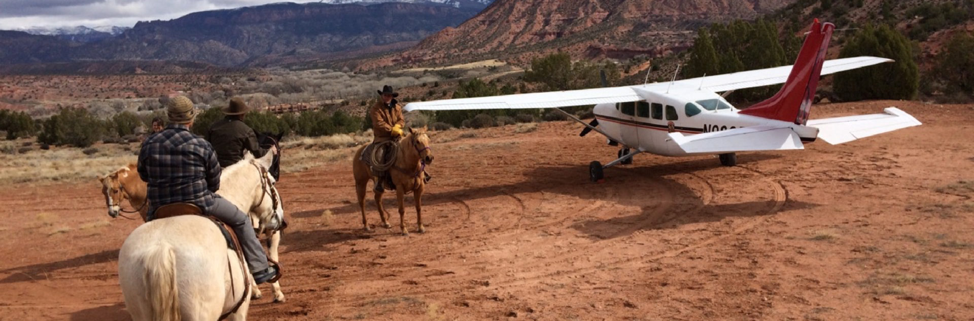 Three people on horses next to a plane in Moab