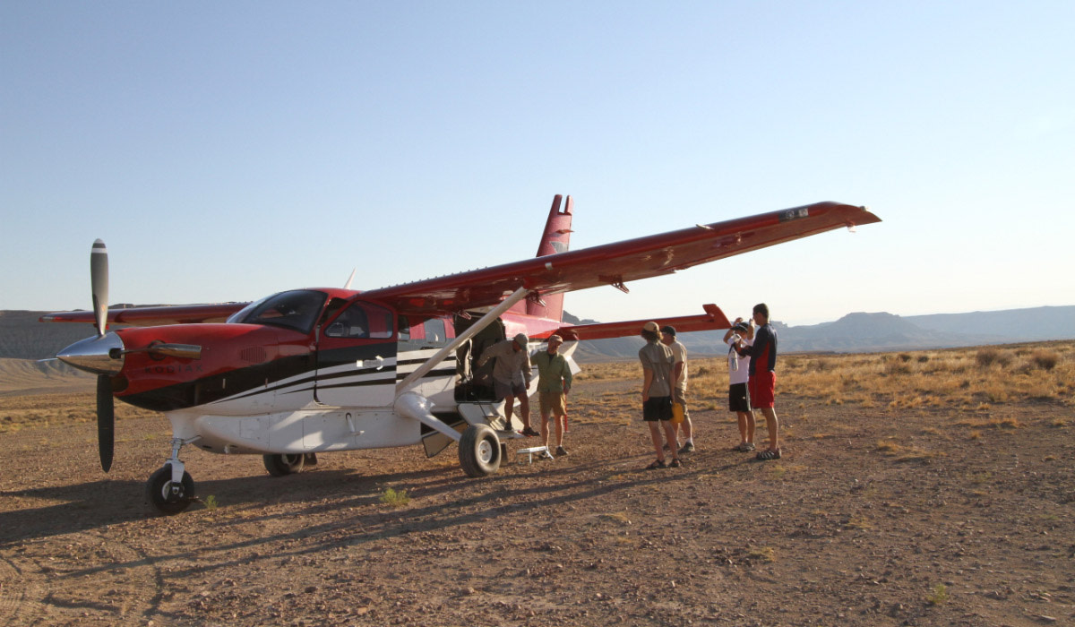 People standing by a white and red airplane in Moab